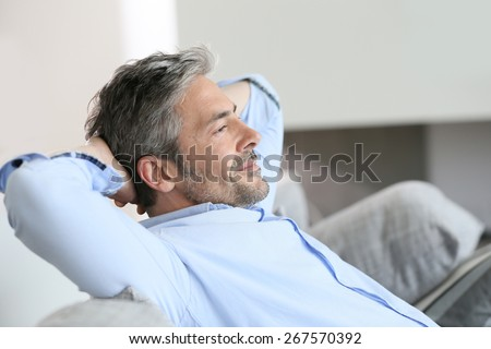 Middle-aged man having a restful moment relaxing in sofa - stock photo