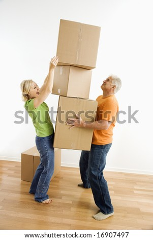Middle-aged man holding stack of cardboard moving boxes while woman places another one on. - stock photo