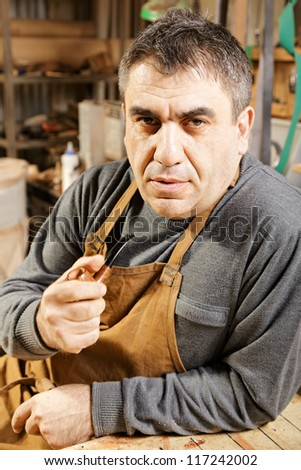 Middle-aged man in apron holding smoking pipe sitting at workbench in his workshop - stock photo