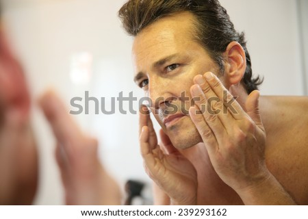 Middle-aged man in bathroom applying facial lotion - stock photo