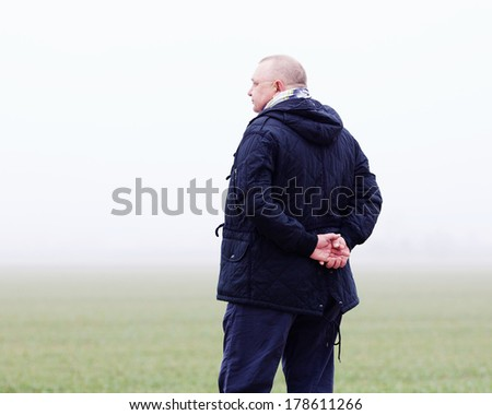 Middle aged man in black coat and scarf standing in foggy field with hands behind his back - stock photo