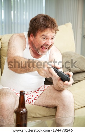 Middle aged man in his underwear playing video games and drinking beer.   - stock photo