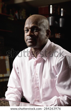 Middle-aged man in pink shirt sitting at the table - stock photo