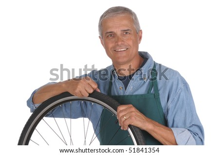 Middle aged man leaning on bicycle wheel that is removed from bike isolated over white. Man is smiling at camera sot in horizontal format - stock photo