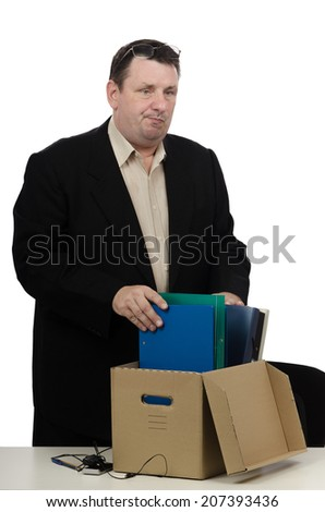 Middle aged man lost his job in local credit union. Man packing belongings into cardboard box on white background - stock photo