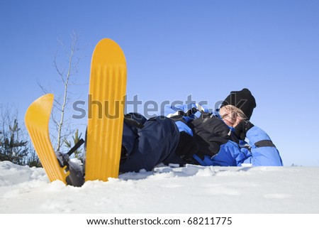 Middle-aged man lying in snow - stock photo
