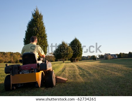 Middle aged man on zero turn mower cutting grass on a sunny day with the sun low in the sky - stock photo