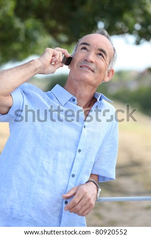 Middle-aged man outdoors with mobile telephone - stock photo