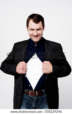 Middle aged man pulling his shirt open - stock photo