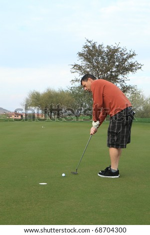 middle-aged man putts a golf ball on the green - stock photo