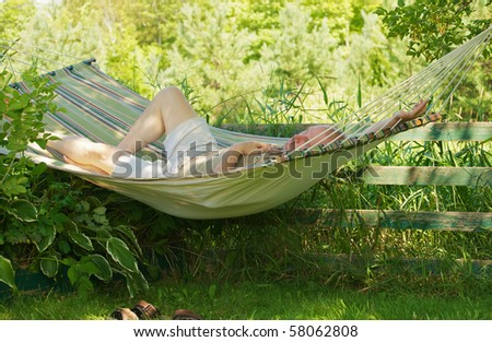 Middle aged man relaxing in a hammock in the shade on a hot summer day. - stock photo