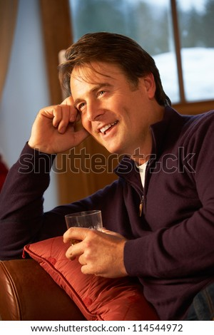 Middle Aged Man Relaxing Sitting On Sofa Drinking Whisky