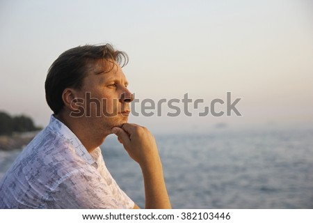 Middle-aged man sitting close to the sea and thinking  - stock photo