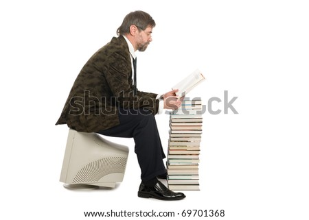 Middle-aged man sitting on an old monitor and reads a book. Book instead of a computer. - stock photo