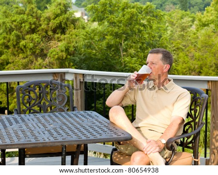 Middle aged man sitting on cast aluminium garden table on deck and drinking a glass of beer in back yard