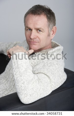 Middle Aged Man Sitting On Sofa