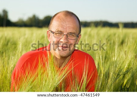 Middle-aged man smiling behind hay - stock photo