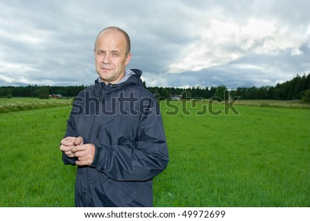 Middle-aged man standing on a field - stock photo