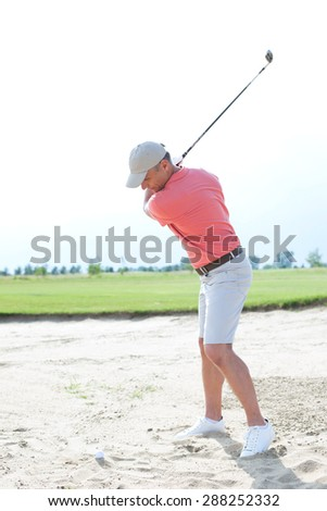 Middle-aged man swinging at golf course against clear sky - stock photo