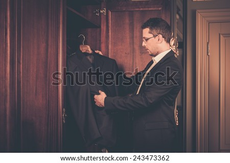 Middle-aged man taking suit from wardrobe  - stock photo