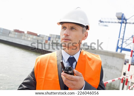Middle-aged man using walkie-talkie in shipping yard - stock photo