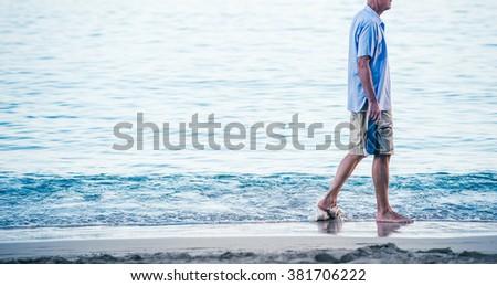 Middle aged man walking lonely coast - stock photo
