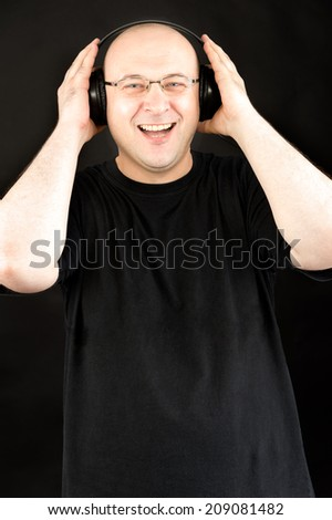 middle aged man wearing headphones and listening music wearing black tshirt against black background  - stock photo