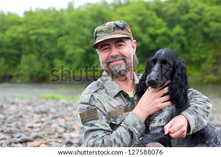 Middle aged man with a dog (Russian Hunting Spaniel). At river in the rain. - stock photo