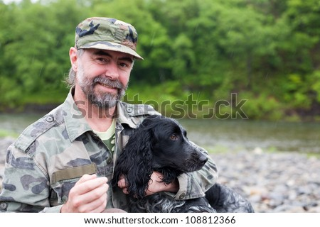 Middle aged man with a dog (Russian Hunting Spaniel). At the river. Rain. - stock photo