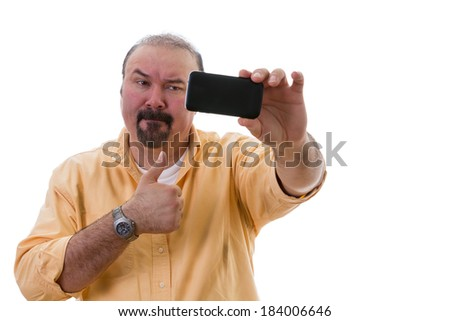 Middle-aged man with a goatee standing posing while taking a self portrait on his mobile as he gives a thumbs up of approval with a frown as though reluctant to do so, isolated on white - stock photo