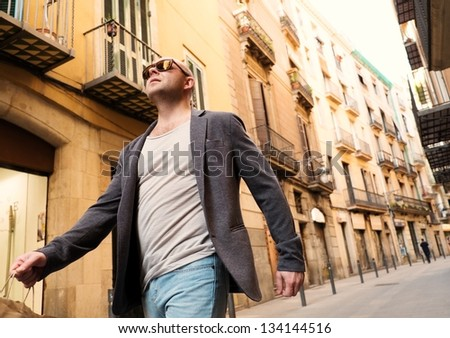 Middle-aged man with shopping bag walking outdoors - stock photo