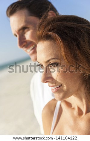 Middle aged man & woman couple together in sunshine on a beautiful tropical beach - stock photo