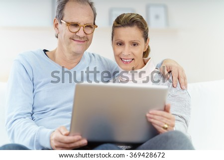 middle-aged married couple using laptop at home