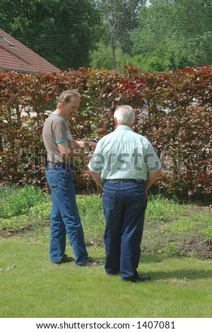 Middle aged men talking in the garden, progress of the growth is topic of talk.