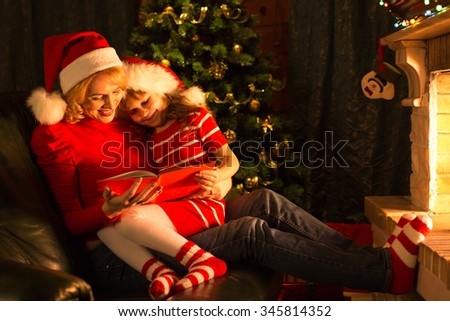 Middle-aged mother and her child daughter reading a book by a Christmas tree in cozy living room in winter - stock photo