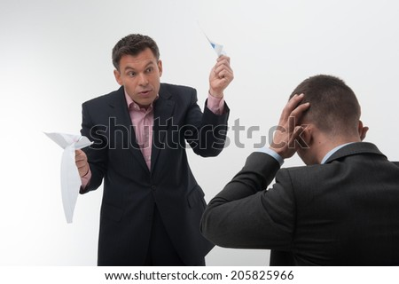 Middle aged office worker in elegant suit tears paper in front of his young colleague sitting from behind holding his head, isolated on white