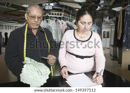 Middle aged owners with notepad calculating bills at laundry counter