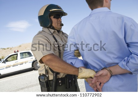 Middle aged policeman arresting a young caucasian man - stock photo