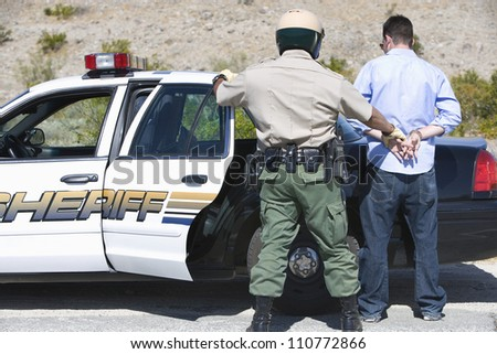 Middle aged policeman arresting a young man - stock photo