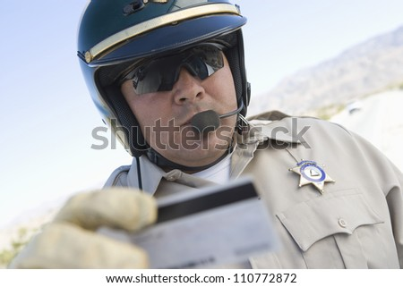 Middle aged policeman checking license - stock photo