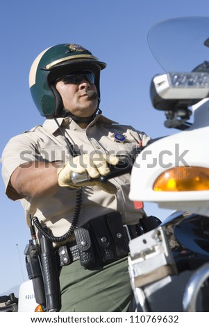 Middle aged policeman riding bike - stock photo