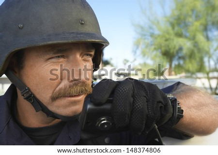 Middle aged policeman using walkie talkie outdoors - stock photo