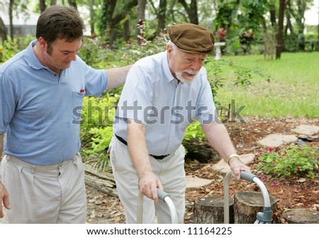 Middle aged son walking beside his disabled elderly father. - stock photo