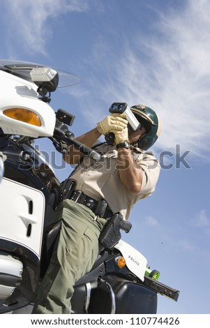 Middle aged traffic officer looking through radar gun from below - stock photo