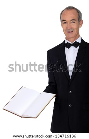Middle-aged waiter holding menu - stock photo