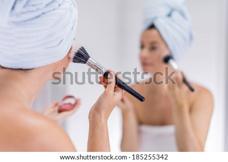 middle aged woman applying makeup - stock photo