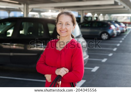 Middle-aged woman at car parking lot. - stock photo