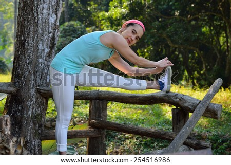 Middle aged woman bending over to do stretching in the park