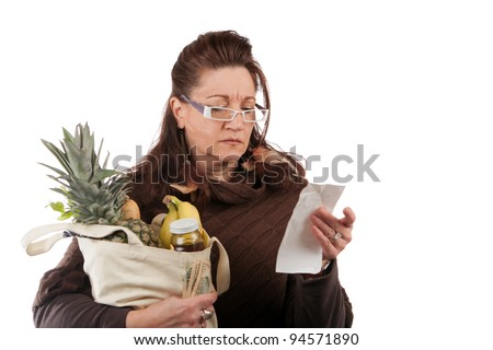 Middle aged woman carefully examining her register receipt reviewing her grocery shopping bill. - stock photo