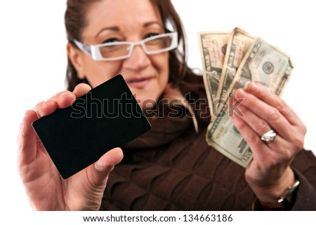Middle aged woman carefully trying to decide between using old fashioned cash or a plastic credit card. - stock photo